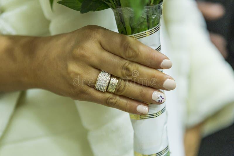 Die Hand der Braut mit dem Verlobungsring und dem Ehering hält einen Blumenstrauß von Blumen lizenzfreies stockbild
