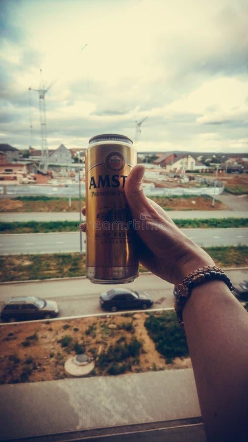 Die Hand der Frau in den Armbändern, die eine Dose Bier auf der Straße halten lizenzfreies stockbild
