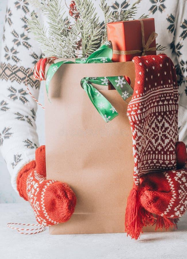 Die Hand der Frau, die eine Papiereinkaufstasche voll Geschenkboxen Weihnachten trägt, verzierte stockfoto
