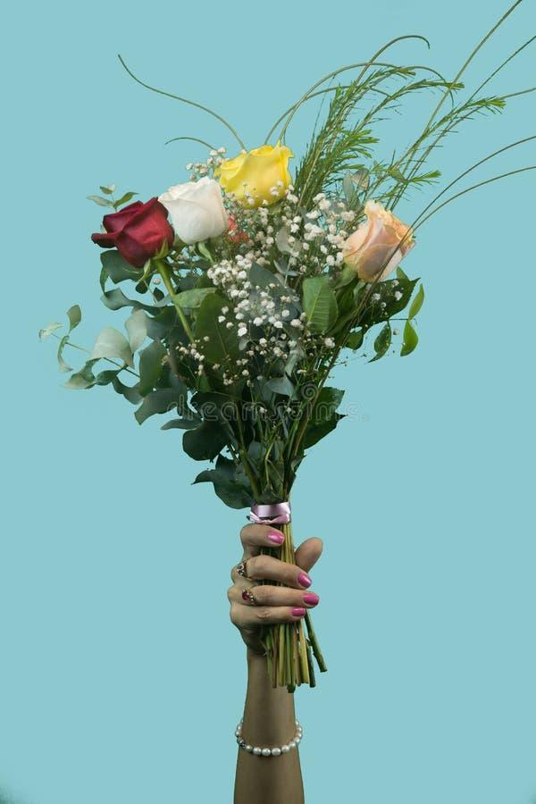 Die Hand der Frau, die einen Blumenstrauß von Rosen hält stockbilder