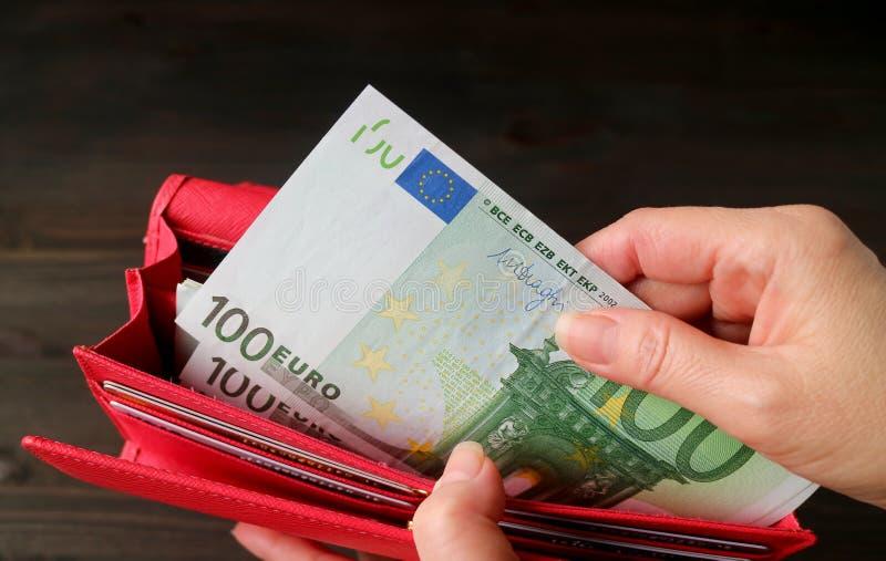Die Hand der Frau, die Eurobanknoten von der roten Geldbörse nimmt stockbild