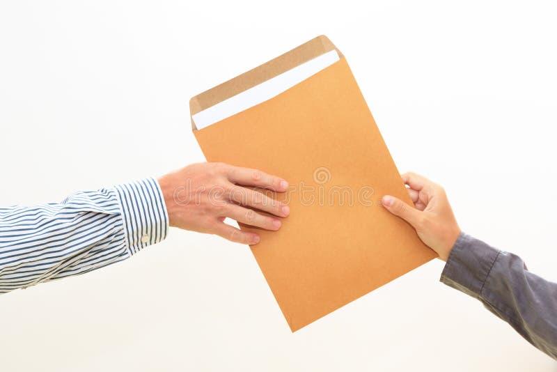 Die Hand der Frau führt Umschlag zur männlichen Hand auf Weiß lizenzfreie stockfotografie
