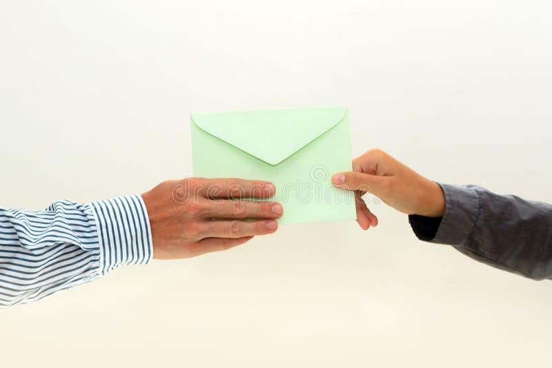Die Hand der Frau führt Umschlag zur männlichen Hand auf Weiß lizenzfreie stockbilder