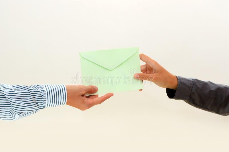 Die Hand der Frau führt Umschlag zur männlichen Hand auf Weiß stockfoto