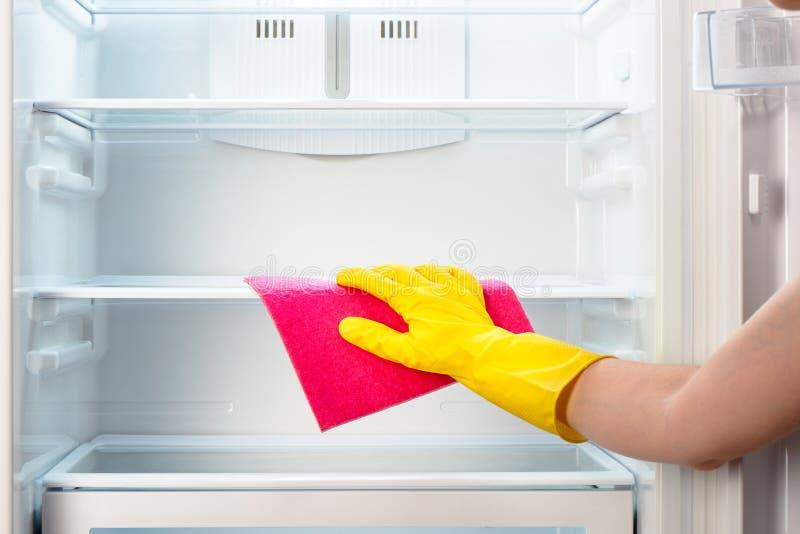 Die Hand der Frau im gelben Handschuhreinigungskühlschrank mit rosa Lappen stockfoto