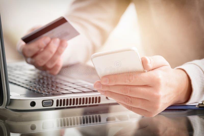 Die Hand der Frau, die Kreditkarte und Smartphone hält stockfotos