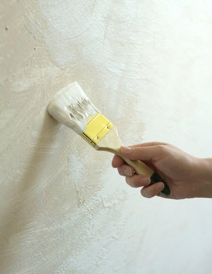 Die Hand der Frau mit Bürste gemalter Wand lizenzfreies stockfoto