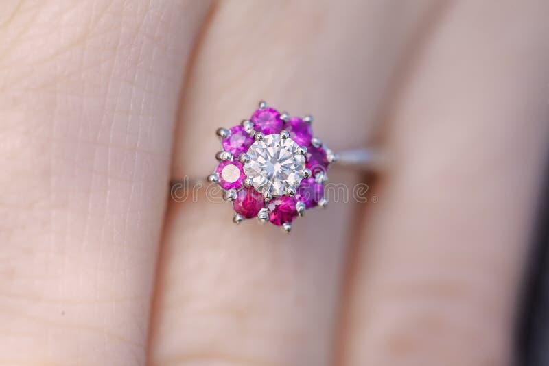 Die Hand der Frau mit einem Rubin-Diamantring lizenzfreie stockbilder