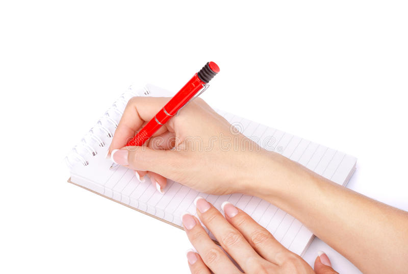 Die Hand der Frau mit einem Stift schreibt in ein lokalisiertes Notizbuch lizenzfreie stockfotografie