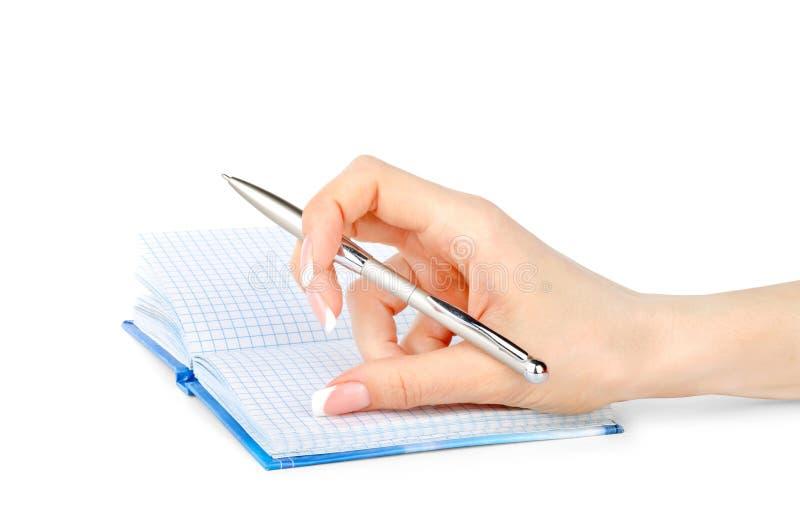 Die Hand der Frau mit einem Stift schreibt in ein lokalisiertes Notizbuch lizenzfreie stockfotos