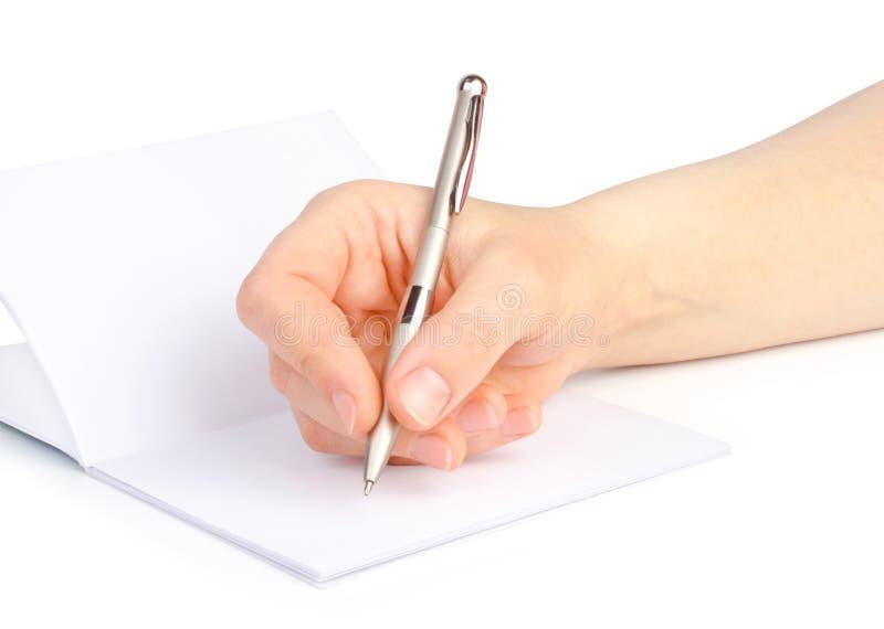 Die Hand der Frau mit einem Stift schreibt in ein Notizbuch lizenzfreie stockfotos