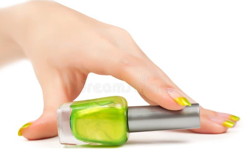 Die Hand der Frau mit einer Flasche grünem Nagellack lizenzfreie stockfotos