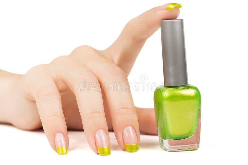 Die Hand der Frau mit einer Flasche grünem Nagellack stockbild
