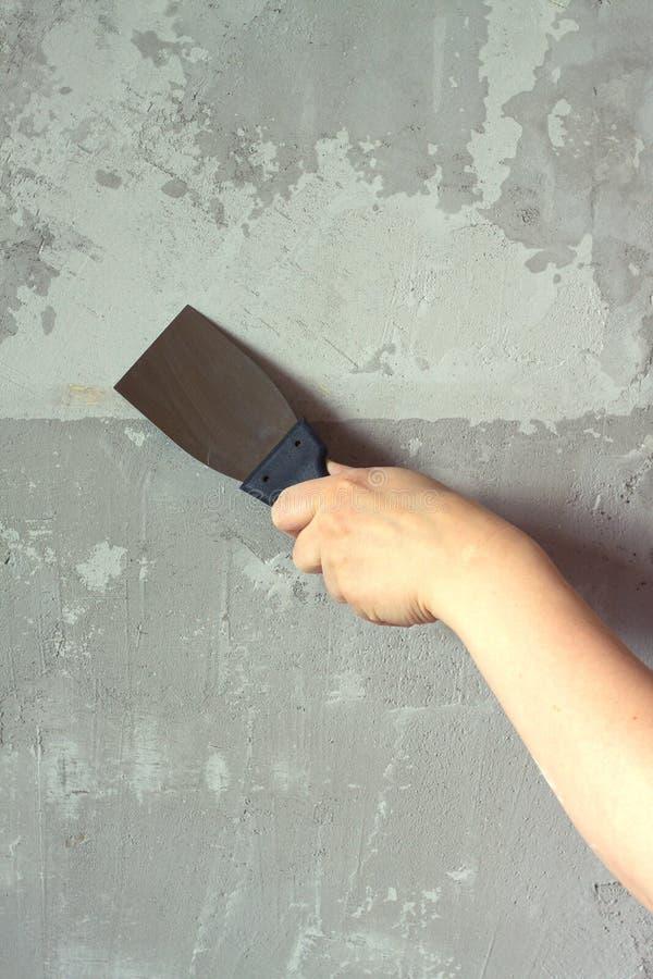 Die Hand der Frau mit einer Spachtel vergipst Betonmauer stockbild