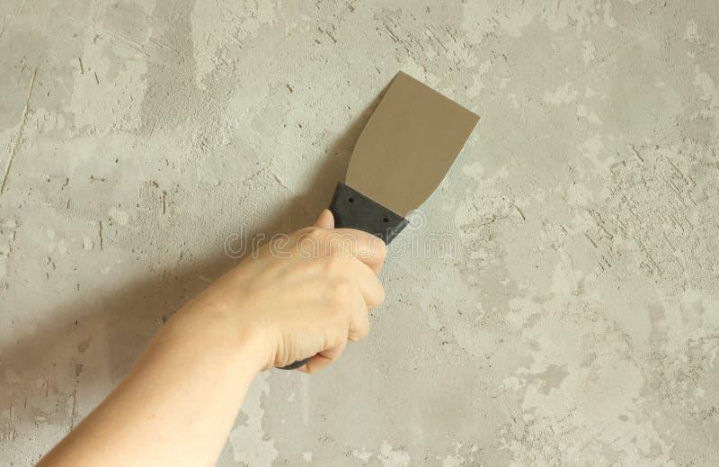 Die Hand der Frau mit einer Spachtel vergipst Wand stockfotografie