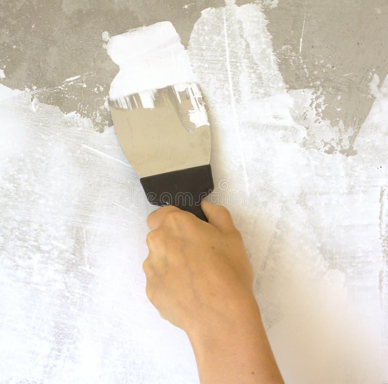 Die Hand der Frau mit einer Spachtel vergipst Wand stockbild