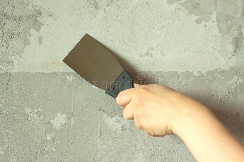 Die Hand der Frau mit einer Spachtel vergipst Wand lizenzfreies stockfoto