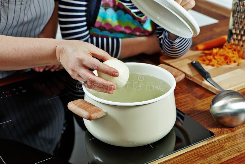 Die Hand der Frau mit der rohen Zwiebel, zum sie in das kochende Wasser zu setzen Geöffnete weiße Kasserolle auf dem schwarzen Of lizenzfreies stockbild