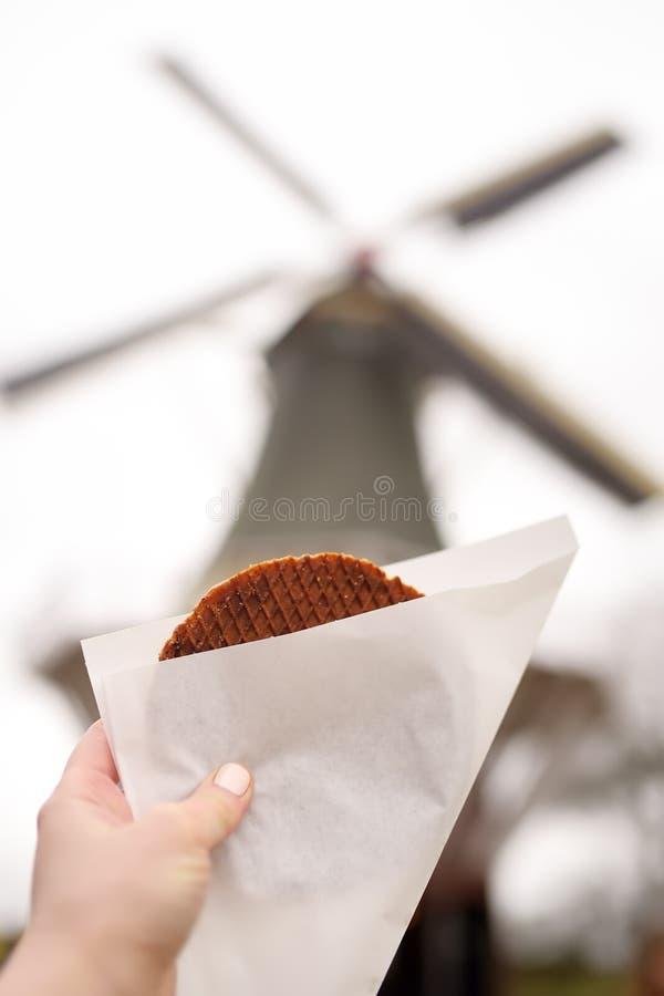 Die Hand der Frau mit traditioneller niederländischer Nahrung - Waffeln mit Karamell auf Hintergrund der niederländischen Windmüh lizenzfreie stockfotos