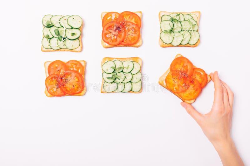 Die Hand der Frau, die Toast mit Tomaten- und chiasamen nimmt stockfoto