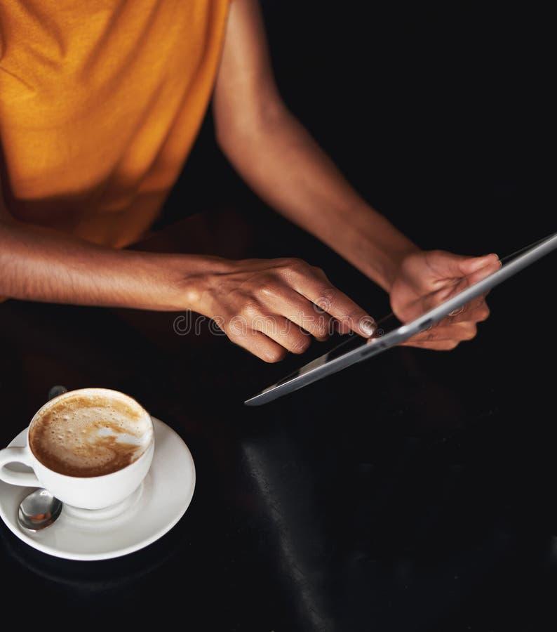 Die Hand der Frau unter Verwendung der digitalen Tablette im Café lizenzfreie stockfotos