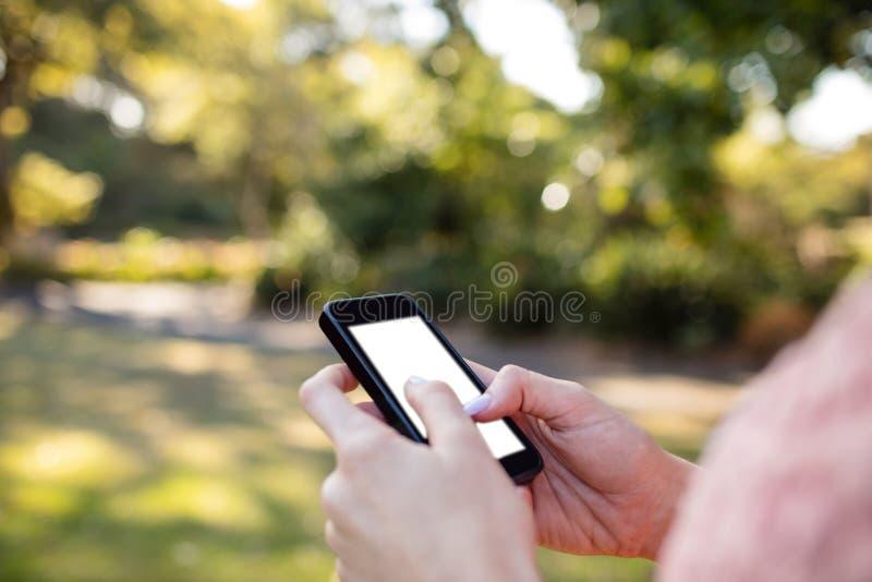 Die Hand der Frau unter Verwendung eines Handys im Park stockfoto