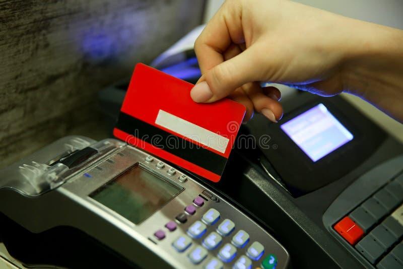Die Hand der Frau zahlt für den Kauf mit einer Karte mit einem Magnetstreifen lizenzfreie stockfotos