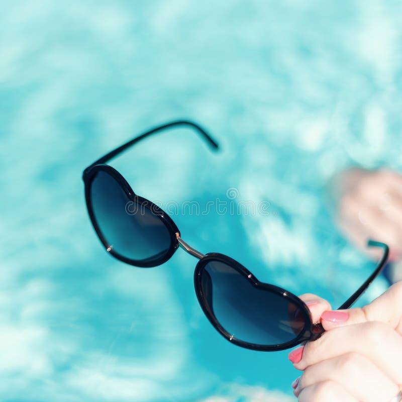 Die Hand der Frauen mit einer schönen Maniküre, die in Form Sonnenbrille des Herzens auf einem Hintergrund gegen das azurblaue Wa stockfotos