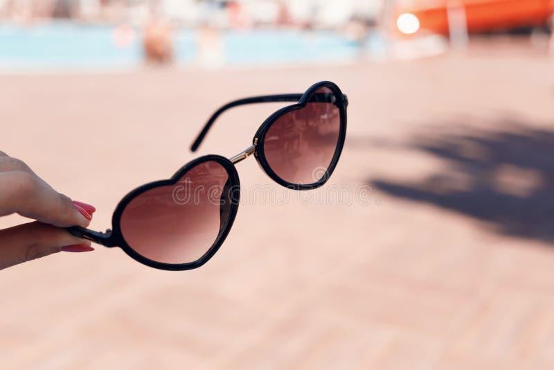 Die Hand der Frauen mit einer schönen Maniküre, die in Form Sonnenbrille des Herzens auf einem Hintergrund des Swimmingpools hält lizenzfreies stockfoto