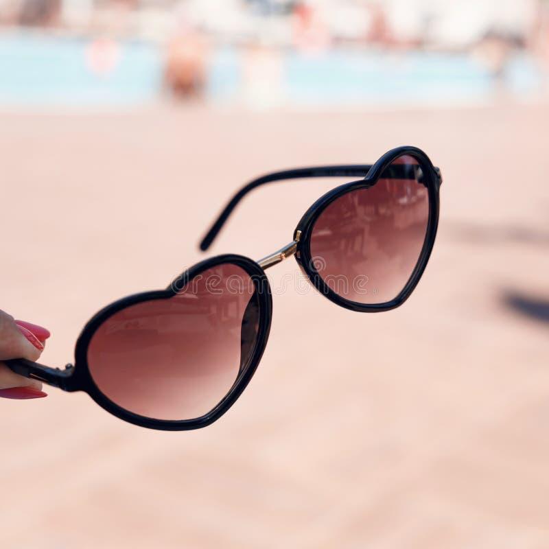 Die Hand der Frauen mit einer schönen Maniküre, die in Form Sonnenbrille des Herzens auf einem Hintergrund des Swimmingpools hält lizenzfreie stockfotos