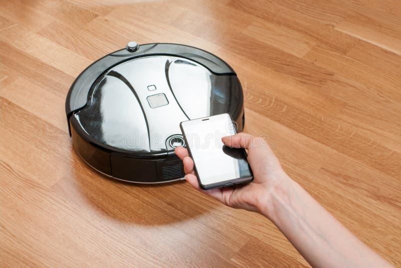 die Hand der Frauen unter Verwendung des Mobiles, zum des schwarzen Roboterstaubsaugers zu steuern moderne intelligente Reinigung stockfotografie