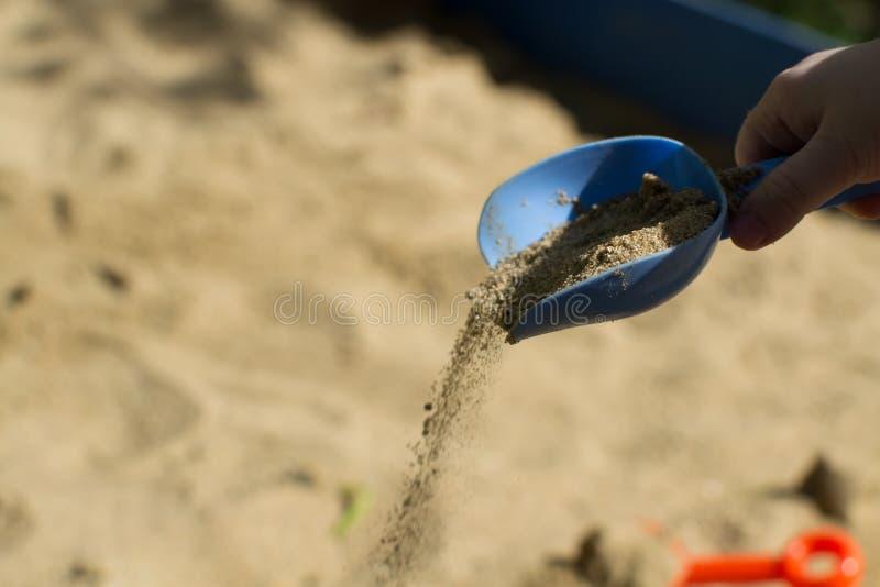 Die Hand der Kinder gießt Sand mit einer blauen Schaufel lizenzfreies stockfoto