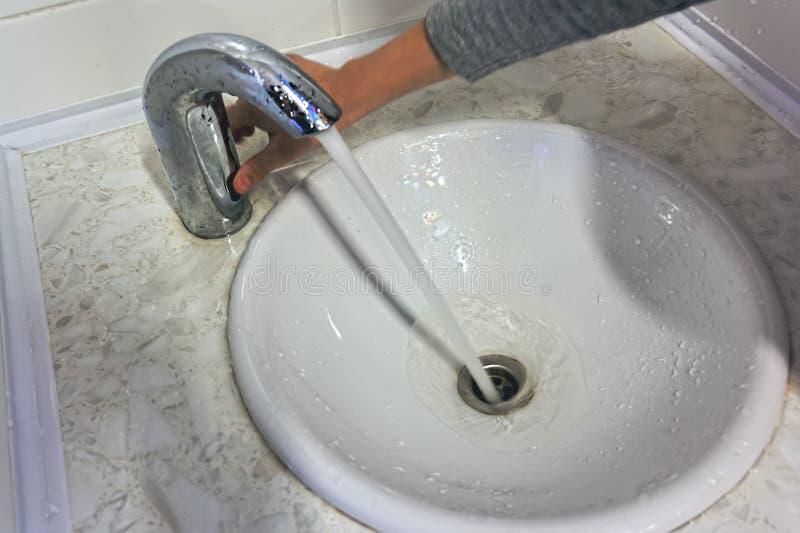 Die Hand der Kinder umfasst ein Knopfmischerwasser im Badezimmer lizenzfreie stockfotos