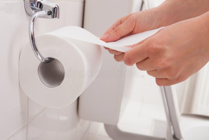 Die Hand der Person unter Verwendung des Toilettenpapiers lizenzfreie stockbilder