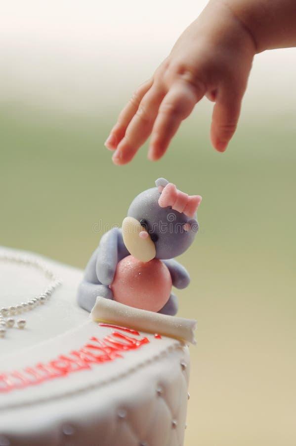Die Hand des Babys und betreffen Kuchen lizenzfreie stockbilder