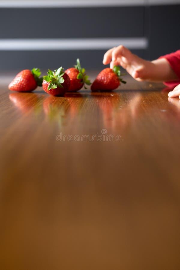 Die Hand des Babys, die verschiedene Früchte auf einem Holztisch manipuliert stockfotos