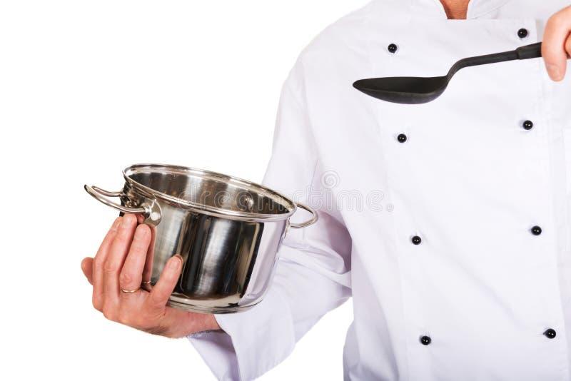Die Hand des Chefs, die Edelstahltopf und -löffel hält stockfotos