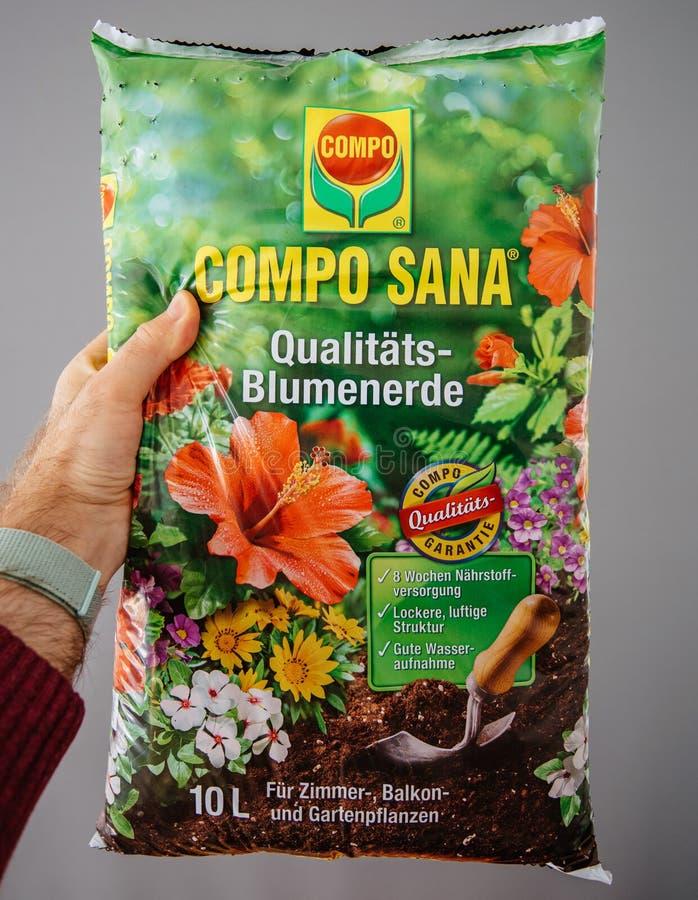 Die Hand des COMPO SANA Qualitats-Blumenerde-Qualit?tsboden-Mannes lizenzfreies stockbild
