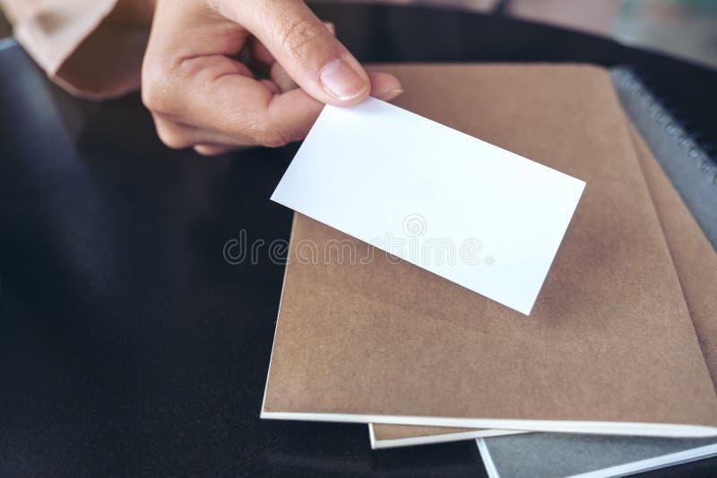 Die Hand des Geschäftsmannes, die leere Visitenkarte mit Notizbüchern auf Tabelle hält und gibt lizenzfreie stockfotos