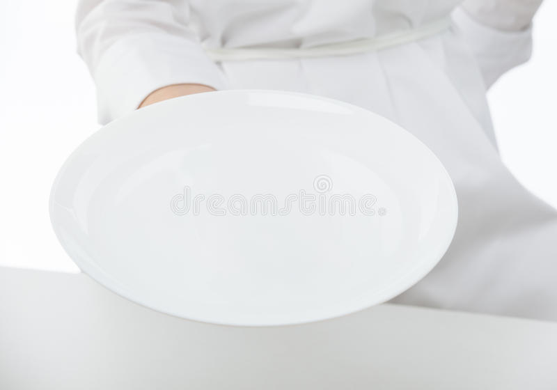 Die Hand des Kochs, die eine leere Platte hält lizenzfreie stockfotos