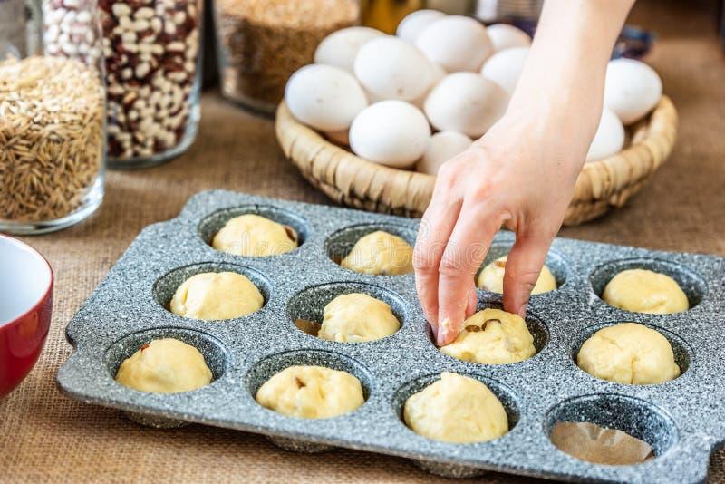 Die Hand des Kochs setzt Teig in Backform des kleinen Kuchens ein stockfoto