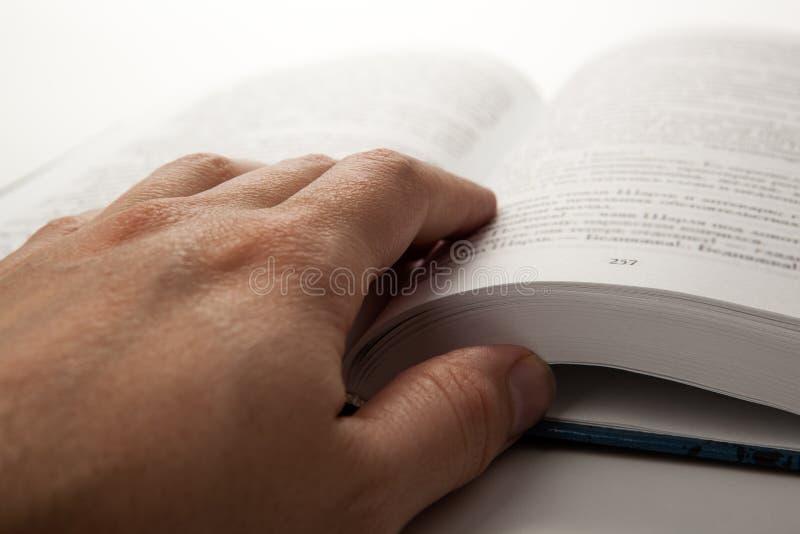 Die Hand des Mannes auf einem offenen Buch mit white pages lizenzfreie stockfotografie