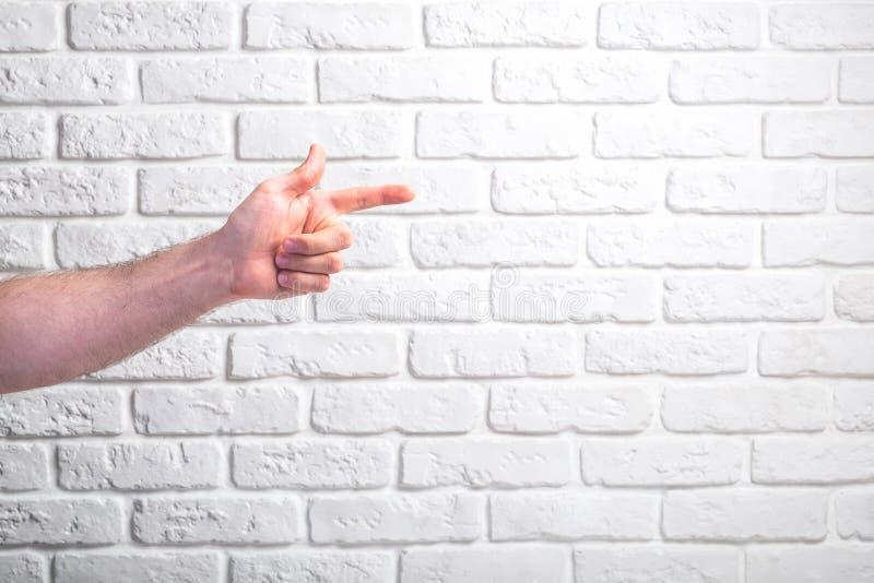 Die Hand des Mannes, die auf weißen Backsteinmauerhintergrund zeigt stockfotos