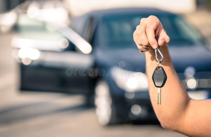 Die Hand des Mannes, die modernes Auto hält, befestigt bereites zur Miete stockbilder