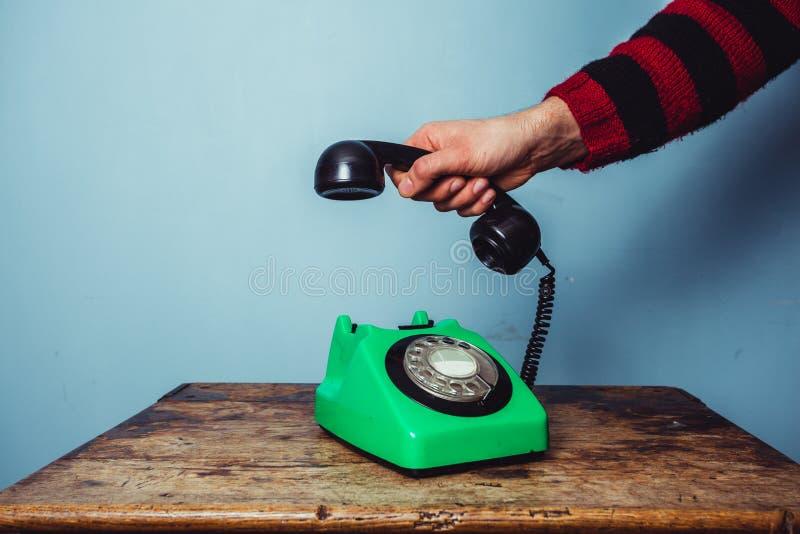 Die Hand des Mannes, die Telefon aufhebt stockfotos