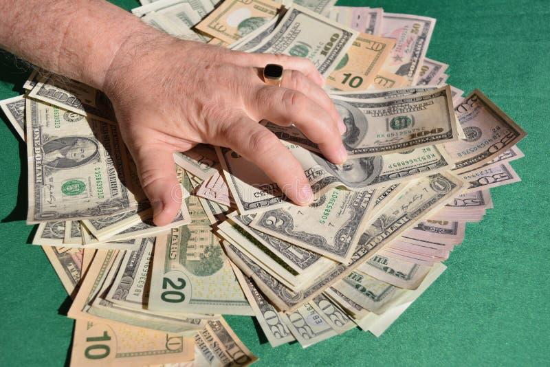 Die Hand des Mannes drückt Dollarscheine zusammen stockbilder