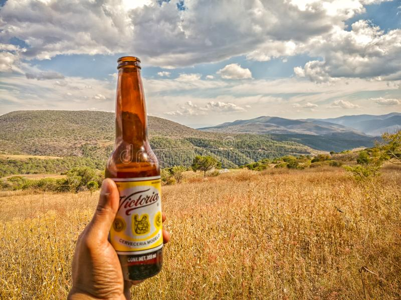 Die Hand des Mannes, die eine mexikanische Bierflasche Victorias, Guerrero-Berge im Hintergrund hält Reise in Mexiko stockbilder