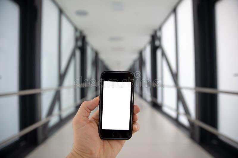 Die Hand des Mannes, die einen Smartphone h?lt Nahaufnahmebild mit vielen reichlichem Kopienraum für Text Handy mit unbelegtem Bi lizenzfreie stockfotografie