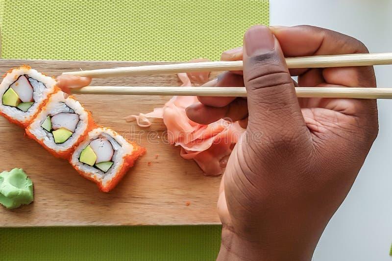 Die Hand des Mannes, die Essstäbchen hält und Kalifornien-Sushirollen auf einem hölzernen Brett isst stockbild