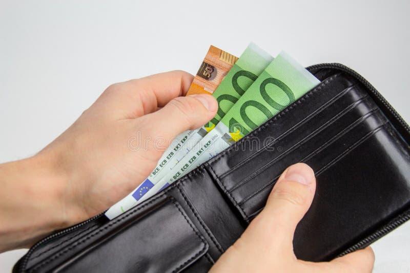 Die Hand des Mannes, die Eurobargeld von der Geldbörse lokalisiert zieht stockbild